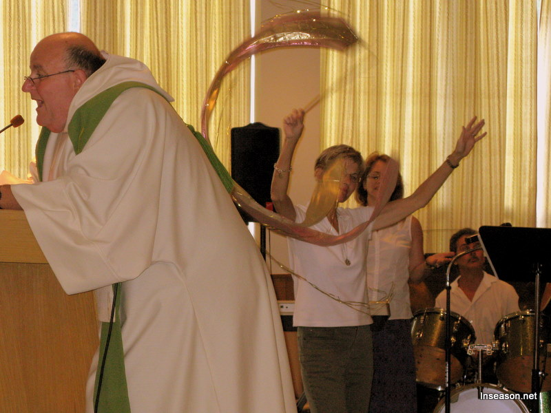 Fr. Tom singing at the podium with worshippers behind at the Espousal Center in Waltham, MA
